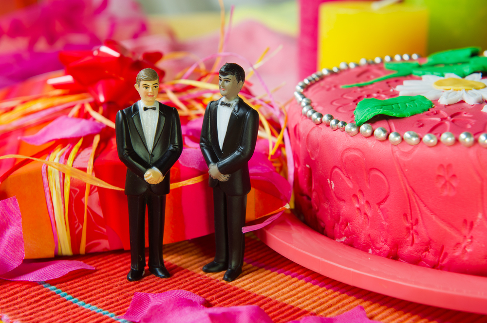 Two groomsmen wedding cake toppers on a festive table decorated for a wedding.