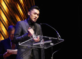 """Nicholas Wong accepts the Lambda Literary Award for his collection of gay poetry, """"Crevasse,"""" published by Kaya Press."""