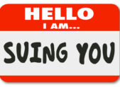 "An image of a name tag that reads, ""Hello, I am suing you."""