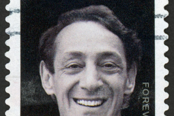 A photo of a postage stamp with Harvey Milk's portrait on it. The photo is in black and white, aside from a small rainbow in the upper left-hand corner.