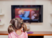 A photo of a young girl in pigtails watching a TV show.