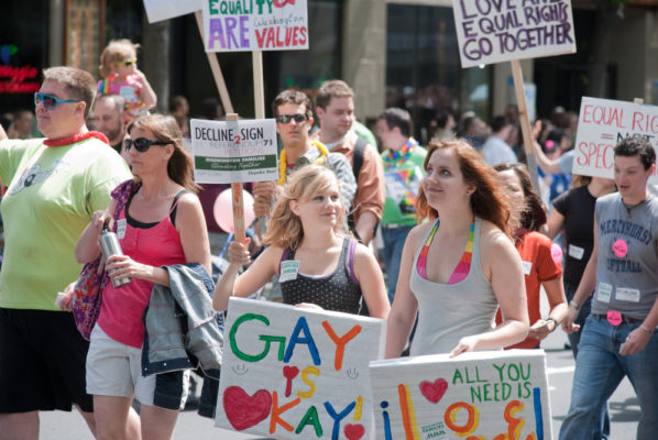 """An image of Seattle's Pride Festival. People are holding numerous signs, including one that reads, """"Gay is okay."""""""