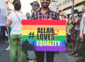 "A photograph of a Muslim man holding a rainbow colored sign that reads, ""Allah Loves Equality."""