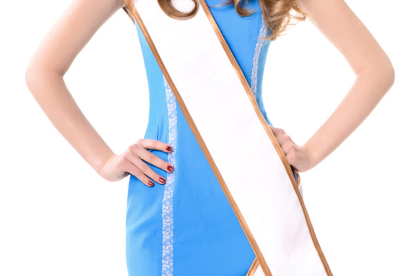 A photo of an attractive young woman wearing a sash.