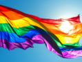 A photo of a rainbow flag flying in the wind.
