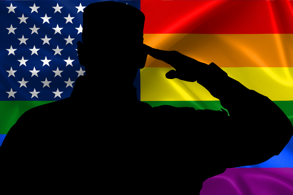 A silhouette of a soldier saluting a rainbow flag.