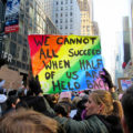 """A photo of a female protestor holding a sign that reads, """"We cannot all succeed when half of us are held back."""""""