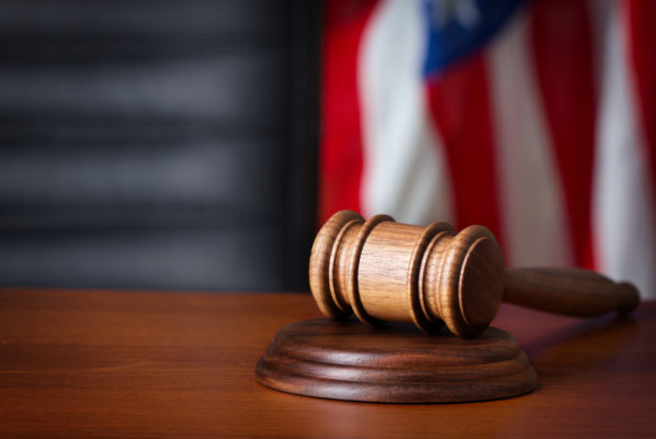 A picture of a gavel with an American flag in the background.