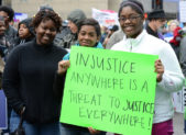 """A photo of three women holding a sign that reads, """"injustice anywhere is a threat to justice everywhere!"""""""