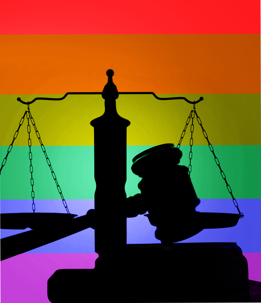 The silhouette of a gavel and the scales of justice juxtaposed against a rainbow background.