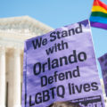 "A photo of a protestor holding a sign that reads, ""We stand with Orlando. Defend LGBT lives."""