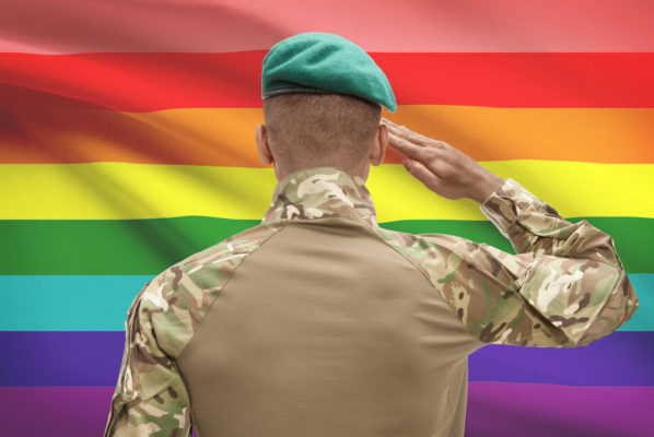 A military service member salutes the rainbow LGBT flag.
