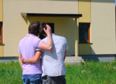 A homosexual couple embrace one another in front of their home.