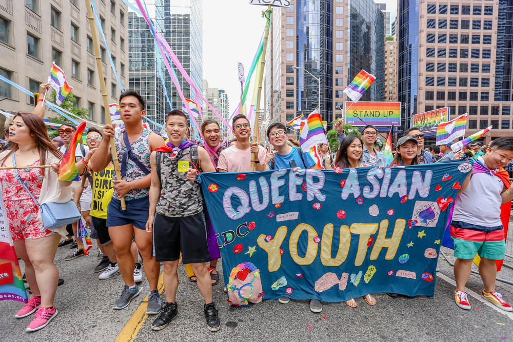 "A group of LGBT activists march through the streets with a sign that reads, ""Queer Asian youth."""