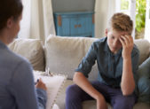 A teenage boy being counseled by a female therapist.