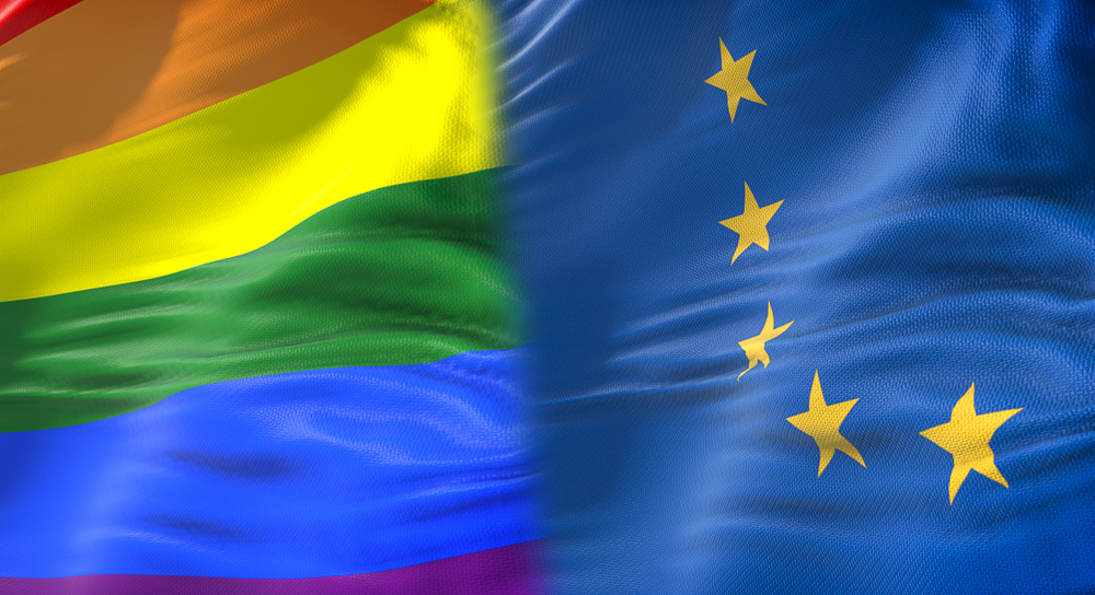 A rainbow flag placed next to the E.U. flag.