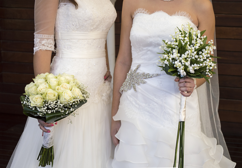 Two women in white wedding gowns holding bouquets.