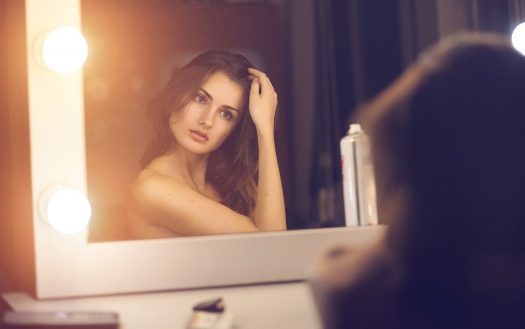 Pretty woman looking in mirror