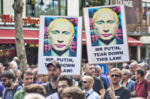 A group of protesters marching in Berlin against anti-gay laws in Russia. Demonstrators carry signs featuring images of President Putin with colors added to make it appear he is wearing make up.
