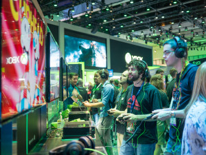 Gamers playing demo XBOX games at E3 2015 expo. Electronic Entertainment Expo, commonly known as E3, is an annual trade fair for the video game industry