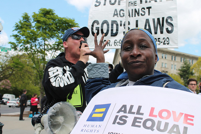 "A marriage equality supporter gestures ""talk to the hand"" to an evangelical opponent in front of the US Supreme Court, April 28, 2015."