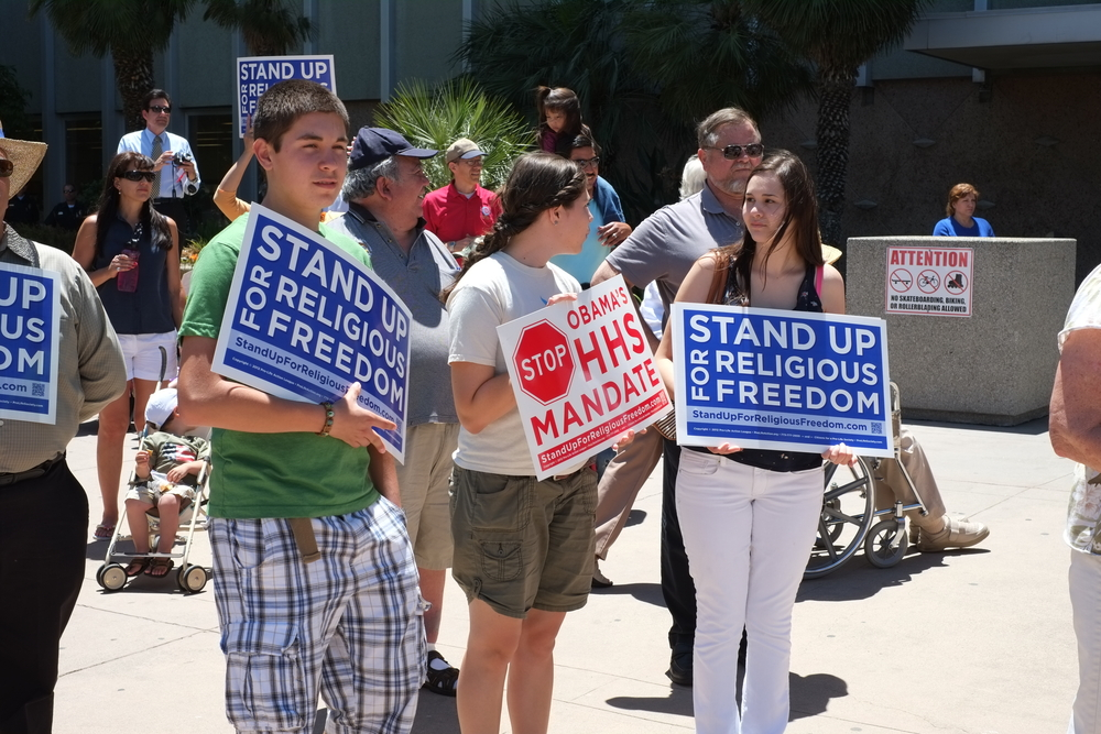 Unidentified participants show protest signs at the Stand Up for Religious Freedom Rally in Bakersfield, CA.