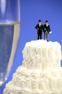 Wedding cake topped with two grooms in top hats.