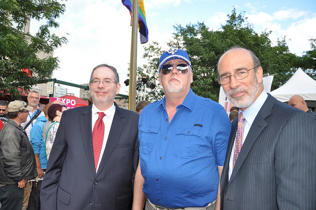 Gilbert Baker, the creator of the Pride Flag, attends a flag raising ceremony at the US Embassy in Canada with Consul General Andrew Parker and Deputy Chief of Mission Richard Sanders.