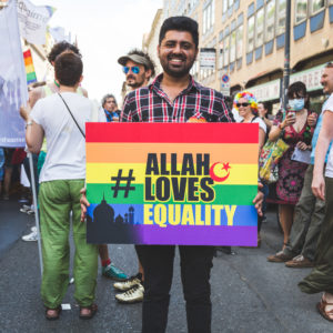 """A photograph of a Muslim man holding a rainbow colored sign that reads, """"Allah Loves Equality."""""""