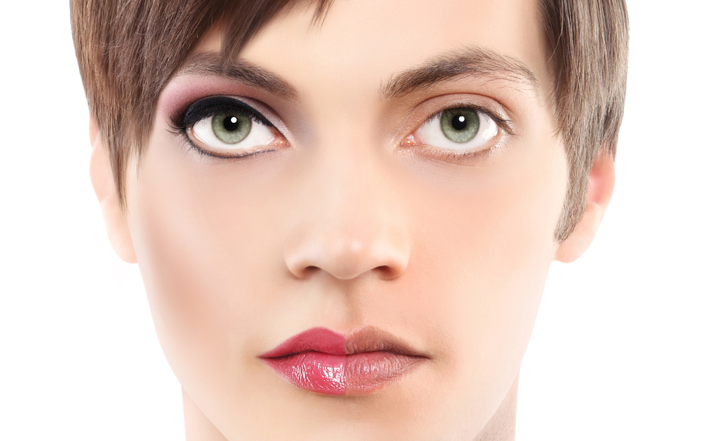 A close-up photo of someone's face. Half of the face looks feminine and is done-up in makeup. The other half of the face is makeup-free and looks masculine.