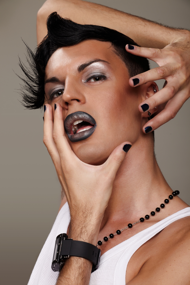 A photo of a man with black hair, black fingernail polish, and dark makeup posing flamboyantly for the camera.