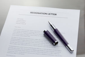 A letter of resignation with a pen on top of it.