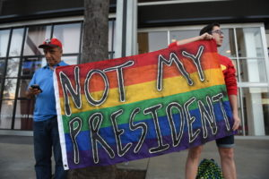 """LGBT protestors hold a sign that reads, """"Not my president."""""""