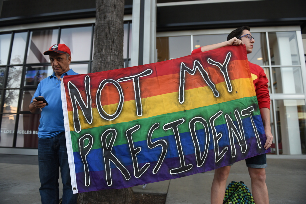 "LGBT protestors hold a sign that reads, ""Not my president."""
