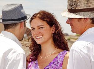 A photo of a woman with two male partners.