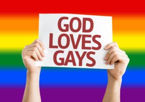 "A person holding up a sign that reads, ""God loves gays."" There is a rainbow in the background."