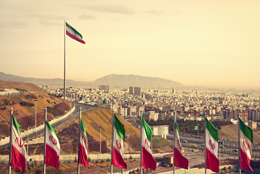 A set of Iranian flags flying in front of the Tehran skyline.