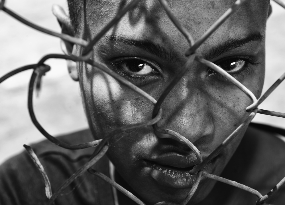 A close-up of an African American behind a fence.
