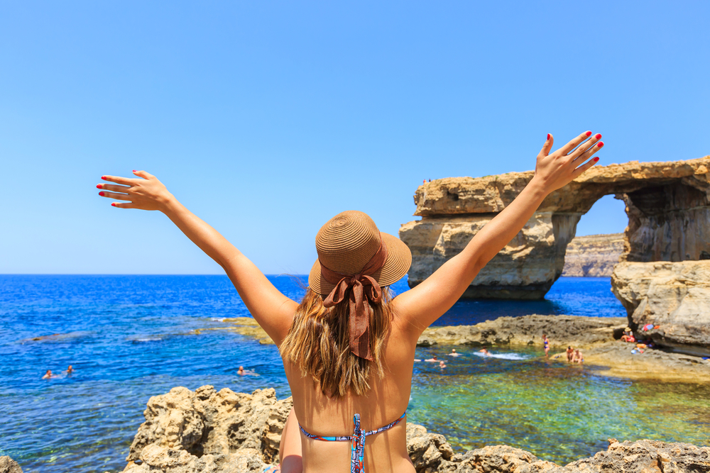 A happy female tourist at a Malta beach.