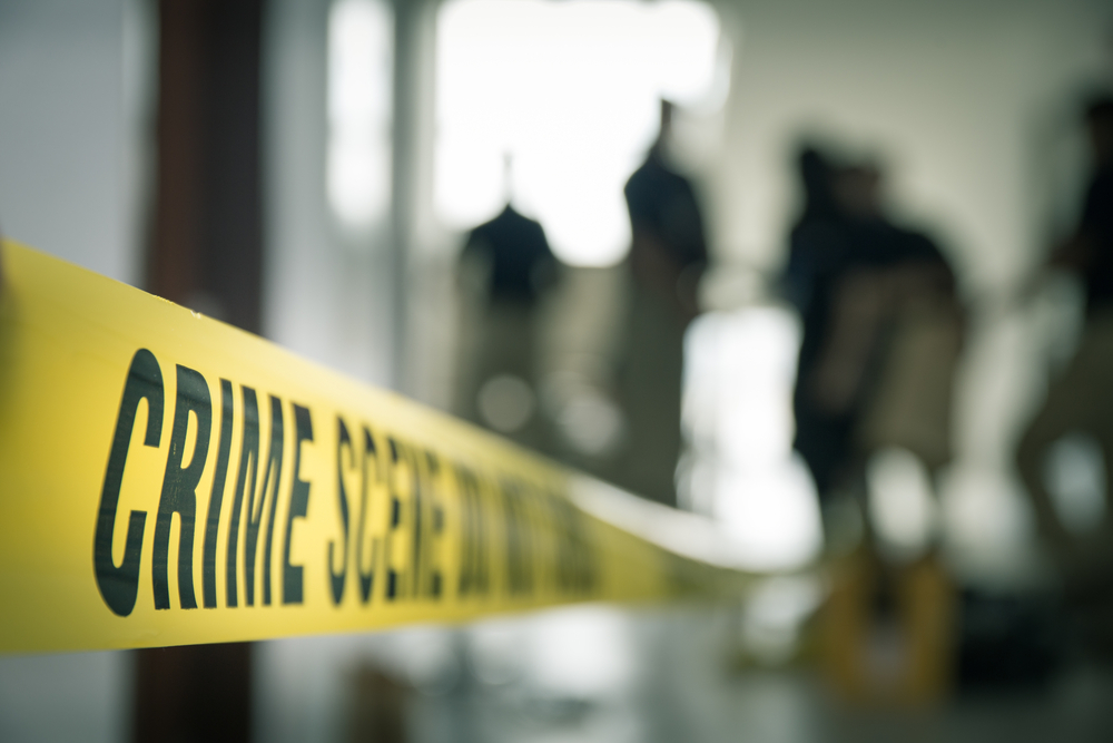 A photo of crime scene tape with blurred figures in the background.