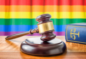 A gavel in front of an LGBT rainbow flag.