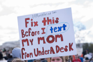 """A National School Walkout demonstrator holds a sign that reads, """"Fix this before I text my mom from under a desk."""""""