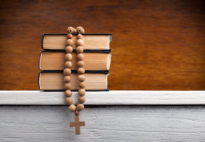 A stack of books with a rosary laid on top.