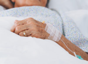 A sick elderly woman in a hospital bed. She is wearing a wedding band.
