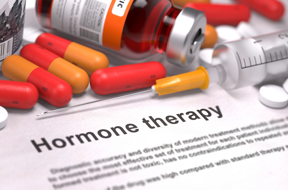 """A sheet of paper that's titled """"Hormone Therapy."""" It is pictured alongside pills and a syringe."""