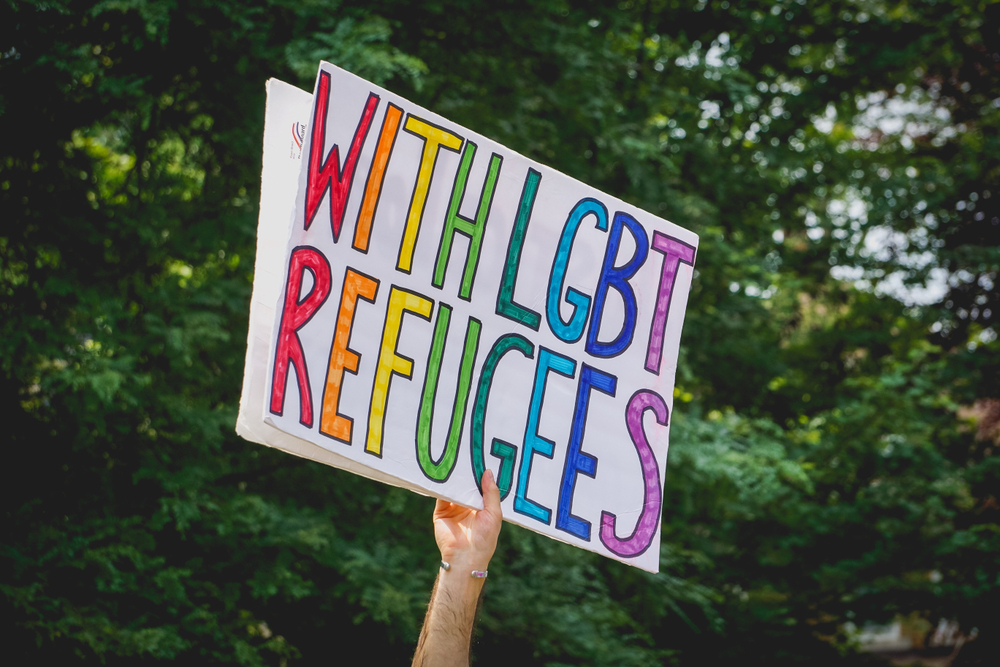 "An activist holds a sign that reads, ""With LGBT refugees."""