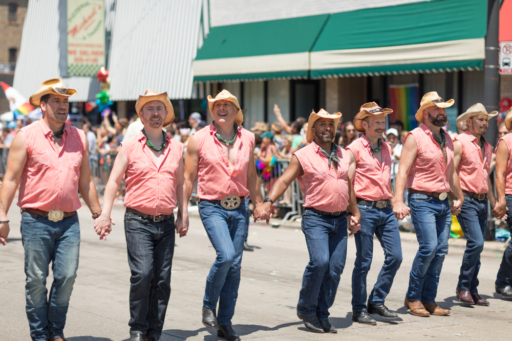 A group of gay cowboys hold hands in celebration of the LGBTQ Pride Parade in Chicago.