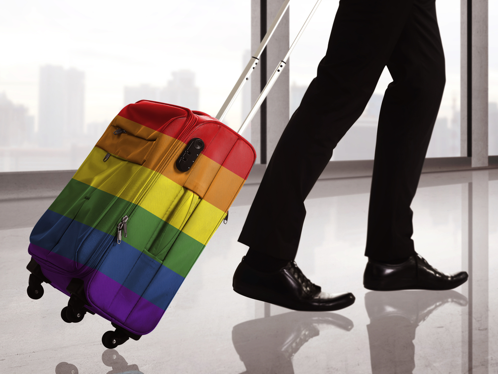 A man traveling through the airport with a rainbow-colored suitcase.