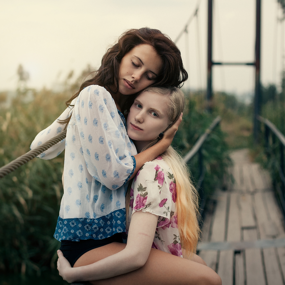 Two lesbians embrace in a rural setting.