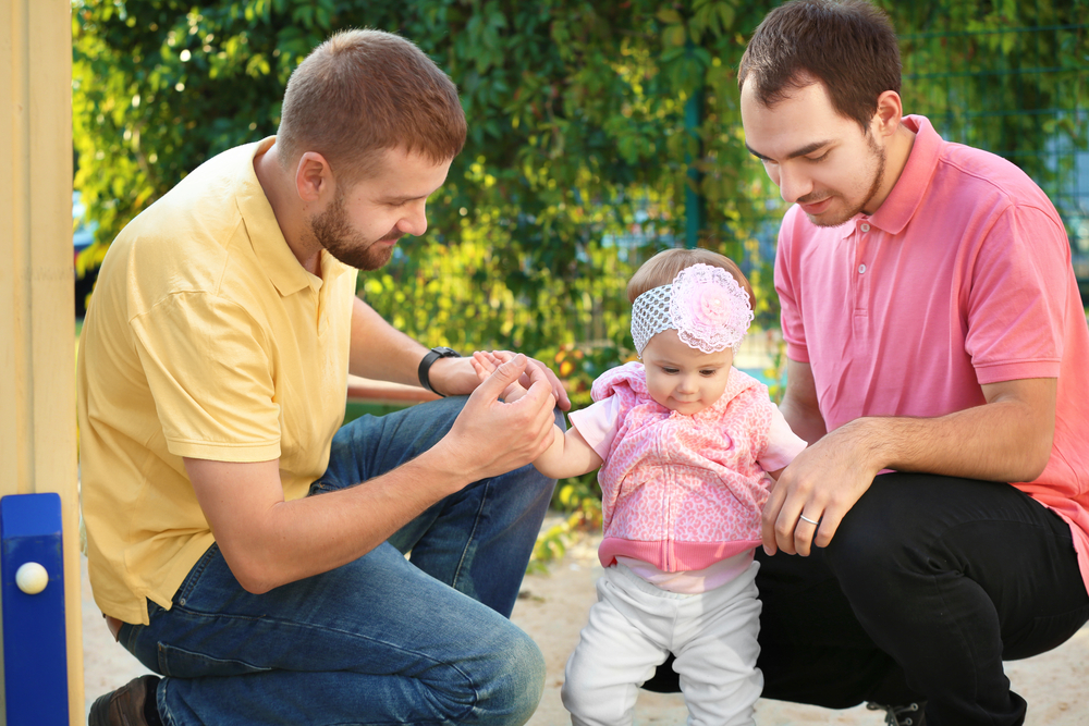A photo of two men caring for an infant girl.